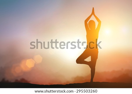 Silhouette Asia woman with Tree Pose yoga on the mountain at pastel sunset background. - stock photo
