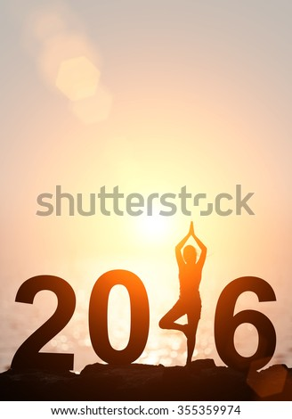 Silhouette Asia woman yoga in 2016 text on the beach at sunset. Happy new year 2016 - stock photo