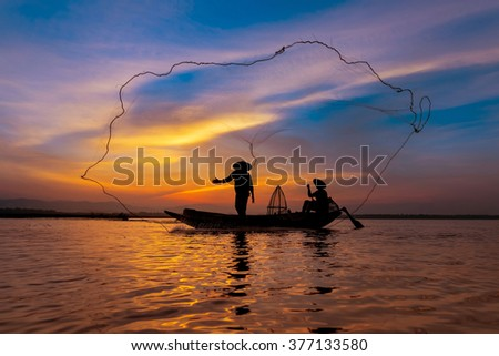 Silhouette asian fisherman on wooden boat casting a net for catching freshwater fish in nature river in the early morning before sunrise - stock photo