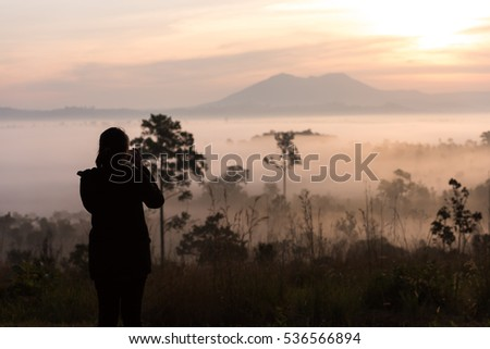 silhouette asian women photography take a photo with beautiful sunrise in environment fog in forest at Thung Salaeng Luang National Park Phetchabun Province,Thailand