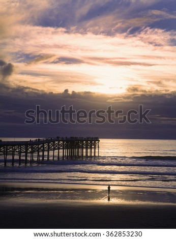 silhouette at sunset at pacific beach pier - stock photo