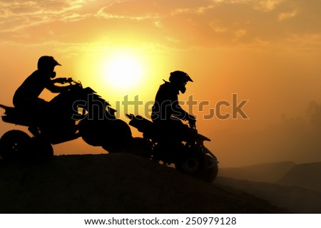 Silhouette ATV or Quad bikes Jump in the sunset. - stock photo