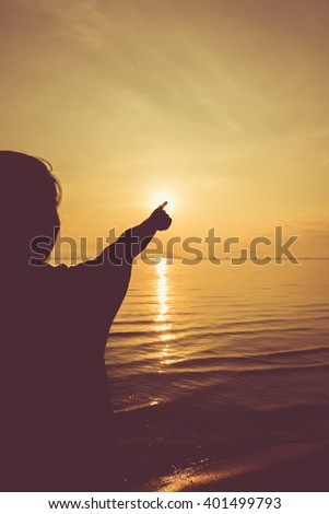 Silhouette back view of woman relax at seaside and pointing to the sun on colorful orange sky background. Vintage picture style. Outdoors.