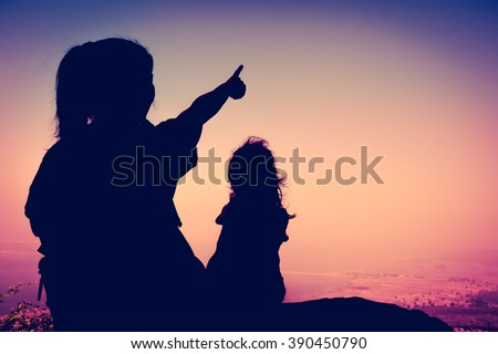 Silhouette back view of young mother and child hikers enjoying the view at the top of a mountain. Woman pointing to empty copy space at sky. Friendly family. Cross process. Vintage picture style. - stock photo