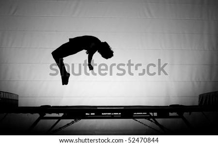 silhouette backflip on trampoline - stock photo