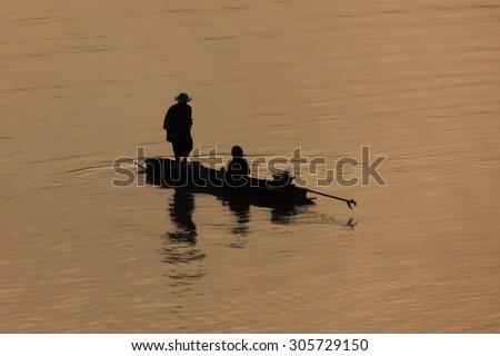 Silhouette background - Fishermen on the boat in sunset time. - stock photo