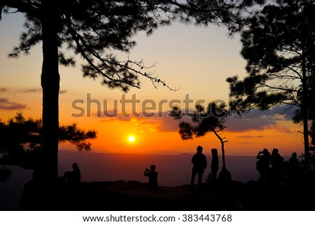 Silhouette backpackers who come to see the sunset at Phu Kradueng National Park,Loei Province,Northeast of Thailand