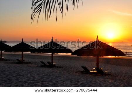 silhouette bed & umbrella with sunrise at Mui Ne beach, Phan Thiet, Vietnam - stock photo