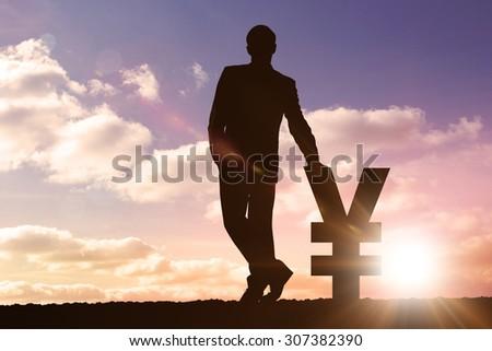 Silhouette beside dollar and yen symbols against sun shining - stock photo