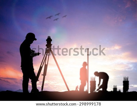 silhouette black man survey and civil engineer stand on ground working in a land building site over Blurred construction worker on construction site. examination, inspection, survey - stock photo