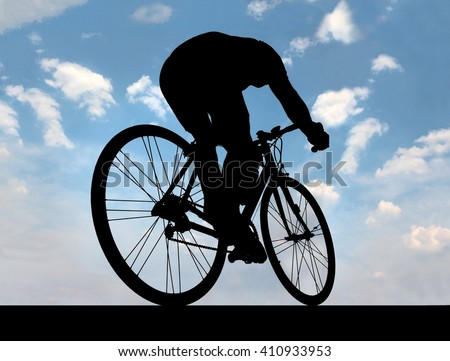 silhouette - Black outline  - of cyclist against the blue sky when he goes on road,