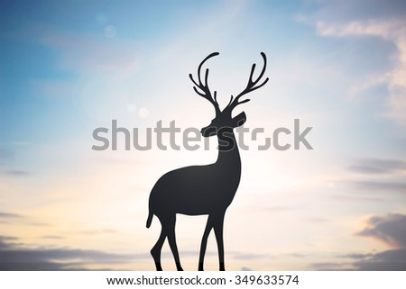 silhouette black reindeer over sunset sky landscape backgrounds for Christmas celebrations decorate concept:xmas backdrop seasonal:merry Christmas festival/new year wallpaper concept.deer with path. - stock photo