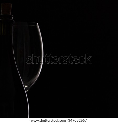 Silhouette bottle and glass on the black background