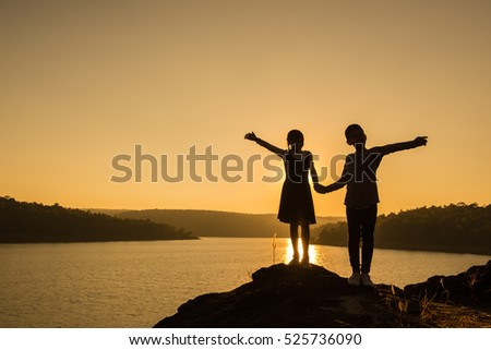Silhouette Boy and Girl holding hands on a stone on the waterfront.on sunset