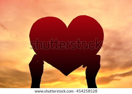 Silhouette boy holding heart shape at sunset