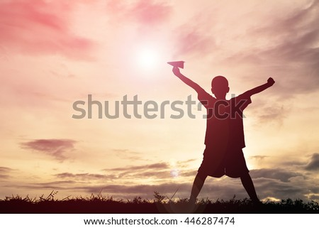 Silhouette boy holding paper rocket on sunset