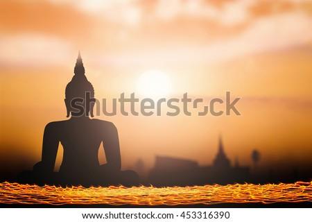 Silhouette Buddha. History, People, Culture, Hope, Spiritual, Thai, Faith, Night, Gold, Fire, Candle, Light, Pray, Temple, Travel, Lent, Lit, Belief, Statue, Wisdom, Asia. - stock photo
