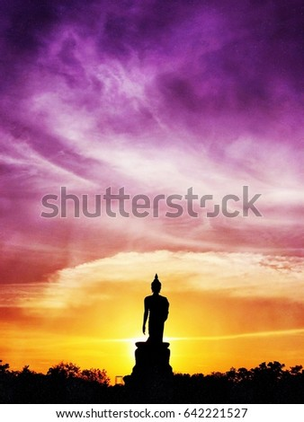 Silhouette Buddha statue in walking posture during colorful sunset at Buddhamonthon Park in Nakhon Pathom province, Thailand