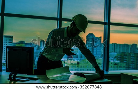 Silhouette builder engineer wear security helmet look at blueprint paper construction drawing plan on background of sunset window frame blue yellow sky with clouds near pc monitor computer - stock photo