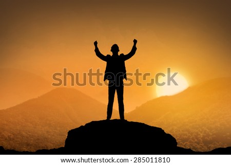 Silhouette business man standing top of the mountain when sunset come - stock photo