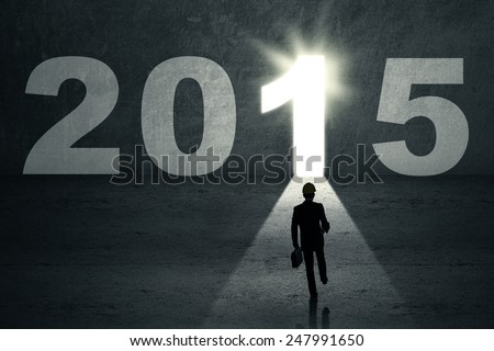 Silhouette businessman carrying briefcase and walk into a future door to his dream in 2015 - stock photo