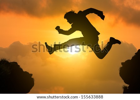 Silhouette businessman jump through the gap with sunset, Business competition concept