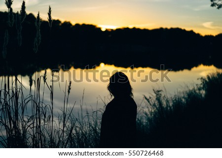 Silhouette by lake at sunset