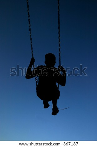 Silhouette child on swings.