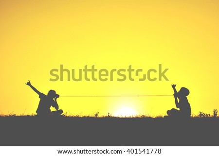 Silhouette children playing string phone at sky sunset - stock photo