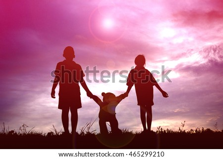 Silhouette children with teddy bear on sunset