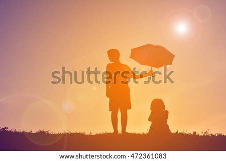 Silhouette children with umbrella on sunset