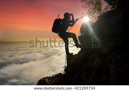Silhouette climbing in the mist goals peak on mountain of sunrise