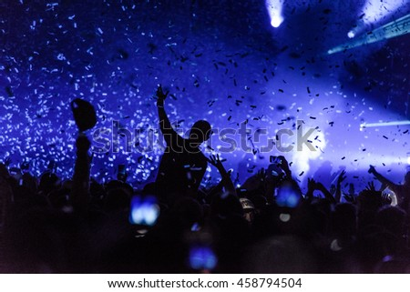 Silhouette Concert Person on Shoulders in Crowd with hands up and Confetti at a Music Festival - Backlit with Lighting.