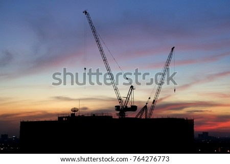 silhouette construction site.tower buliding and crane with city and dusk sky background