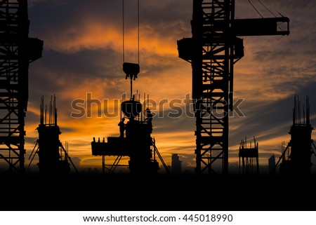Silhouette Construction with workers and building on vibrant sky background - stock photo