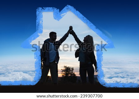 Silhouette couple holding up hands at dusk against blue sky over clouds at high altitude - stock photo