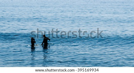 Silhouette couple play in sea