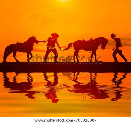 silhouette cowboy and horse with water reflection.on sunset