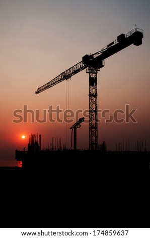 Silhouette crane on top of under construction building at sunset