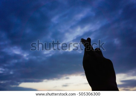 Silhouette crossed fingers with sunset sky