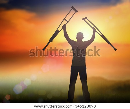 Silhouette disabled man standing up at sunset. Positive concept of cure, recovery, medical miracle, hope, insurance etc.  International Day of Persons with Disabilities, Liberate, Unlock concept. - stock photo