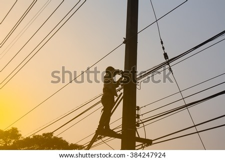 Silhouette, Electrician working at height on poles.