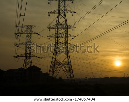 Silhouette electricity pylon against sunrise. - stock photo