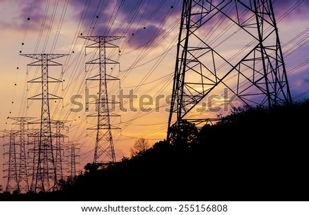 Silhouette electricity pylons in sunset background                                - stock photo