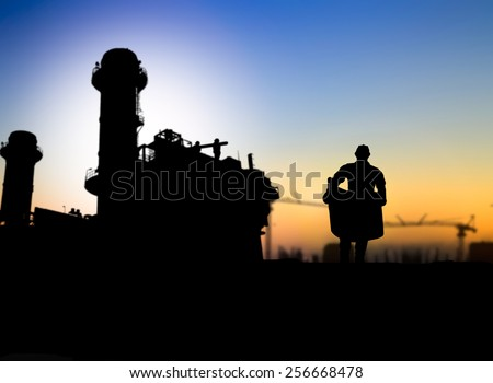 silhouette engineer looking at blueprints in a building site over Blurred  construction site - stock photo