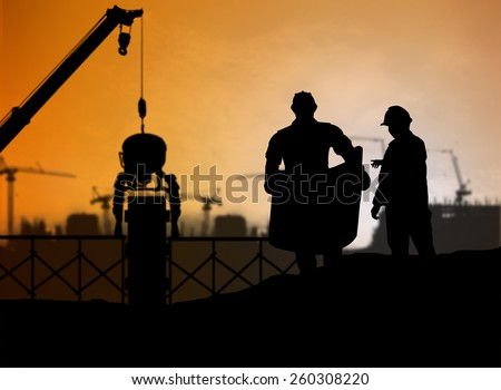 silhouette engineer looking at blueprints in a building site over Blurred construction worker on construction site - stock photo