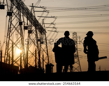 silhouette engineer looking at blueprints over Blurred substation  - stock photo