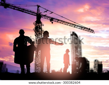 Silhouette engineer looking construction worker under tower crane in a building site over Blurred construction worker on construction site