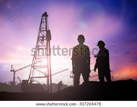 silhouette engineer looking work a building site over Blurred construction worker on construction site - stock photo