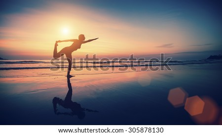 Silhouette exercises girl on the background of the sea and sunset. Fitness and healthy lifestyle.
